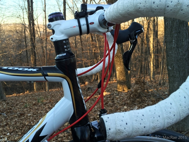 Red shift/brake cable housings and white Fizik handlebar tape.